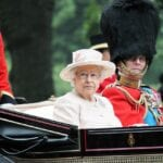 The Queen of England rides in a carriage