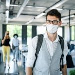 man in mask walking into office